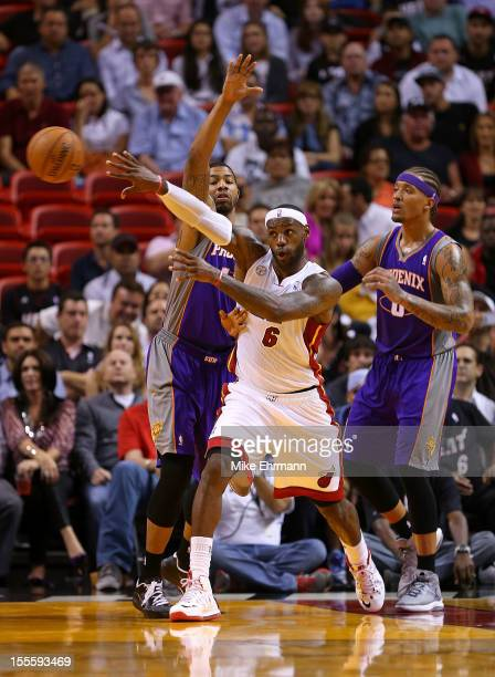 LeBron James of the Miami Heat passes away from Shannon Brown and Michael Beasley of the Phoenix Suns during a game at AmericanAirlines Arena on...