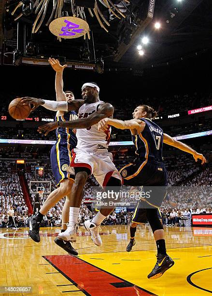 LeBron James of the Miami Heat passes away from Tyler Hansbrough and Louis Amundson of the Indiana Pacers during Game Five of the Eastern Conference...