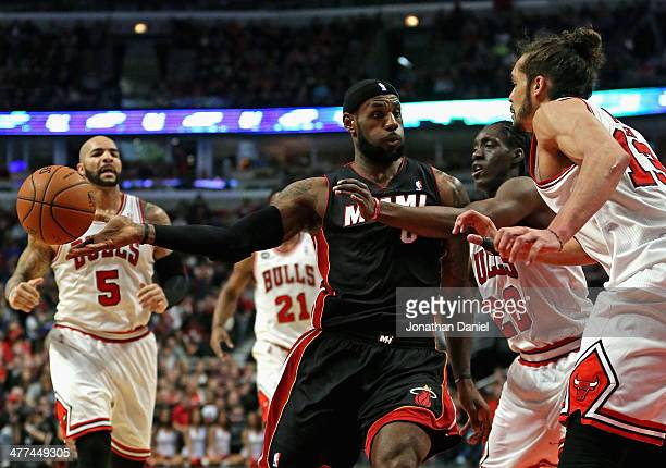 LeBron James of the Miami Heat passes under pressure from Tony Snell and Joakim Noah of the Chicago Bulls at the United Center on March 9 2014 in...