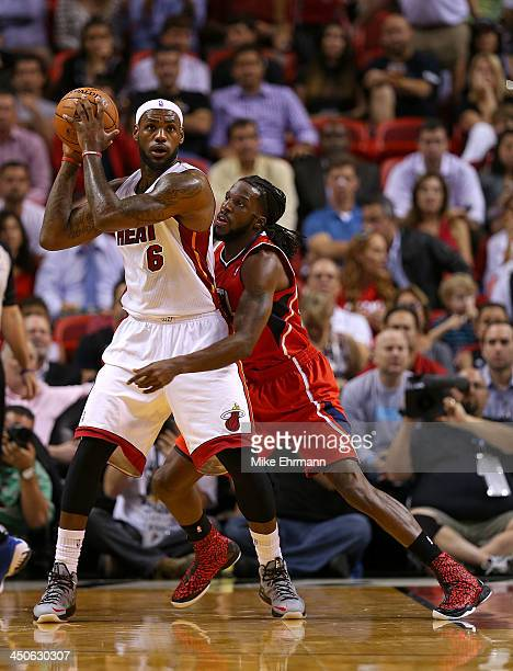 LeBron James of the Miami Heat posts up DeMarre Carroll of the Atlanta Hawks during a game at American Airlines Arena on November 19 2013 in Miami...