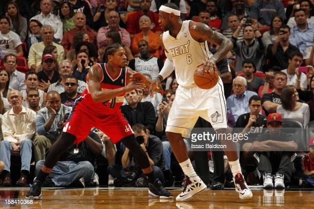 LeBron James of the Miami Heat protects the ball from Cartier Martin of the Washington Wizards during a game between the Washington Wizards and the...