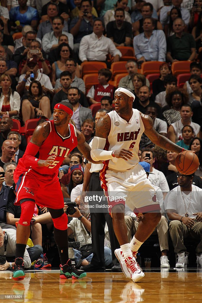 LeBron James #6 of the Miami Heat protects the ball from Josh Smith #5 of the Atlanta Hawks during a game between the Atlanta Hawks and the Miami Heat on December 10, 2012 at American Airlines Arena in Miami, Florida.