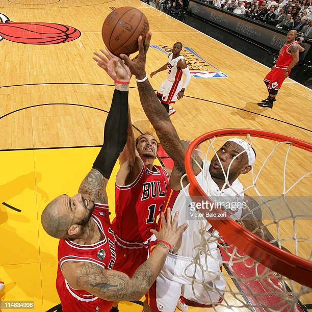 LeBron James of the Miami Heat rebounds against Carlos Boozer and Joakim Noah of the Chicago Bulls during Game Four of the Eastern Conference Finals...