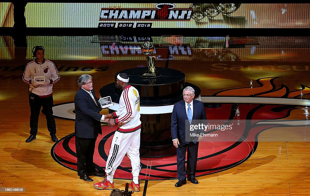 LeBron James of the Miami Heat recieves his 2013 Championship Ring from owner Micky Arrison and NBA commissioner David Stern during a game against...