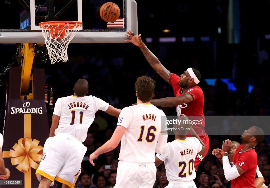 LeBron James of the Miami Heat shoots over Wesley Johnson and Jodie Meeks of the Los Angeles Lakers at Staples Center on December 25 2013 in Los...