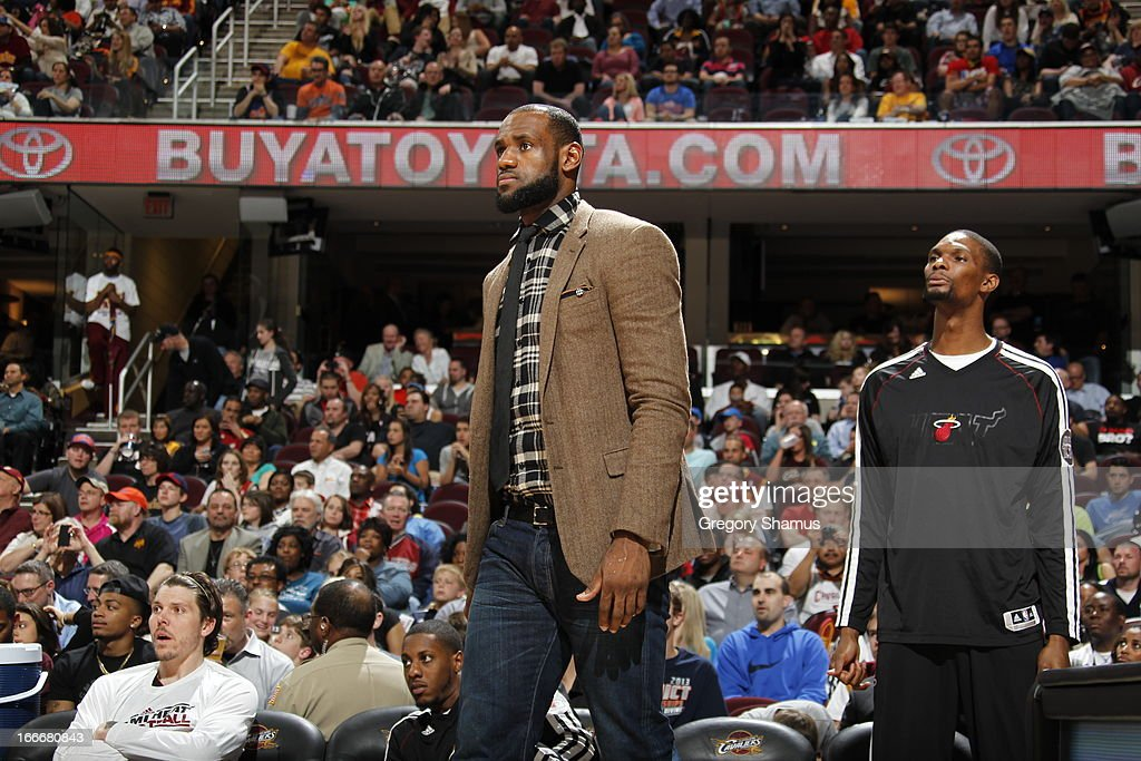 LeBron James #6 of the Miami Heat walks onto the court with street clothing along with Chris Bosh #1 against the Cleveland Cavaliers at The Quicken Loans Arena on April 15, 2013 in Cleveland, Ohio.