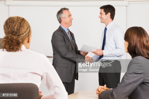 A lecturer handing a certificate to a student