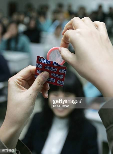 A lecturer shows how to use a condom during a lesson on AIDS prevention at the Sichuan Univerity on November 18 2004 in Chengdu Starting next year...