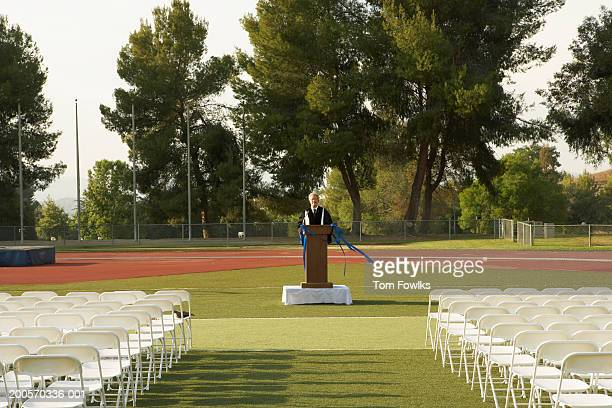 Lecturer standing at podium in front of empty seats outdoors