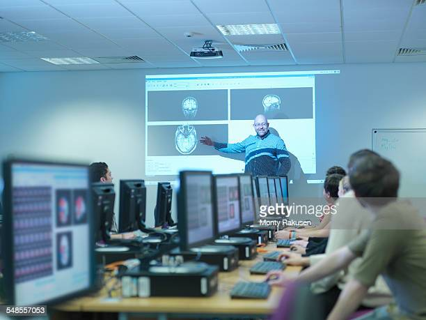 Lecturer teaching neuroimaging students at workstations