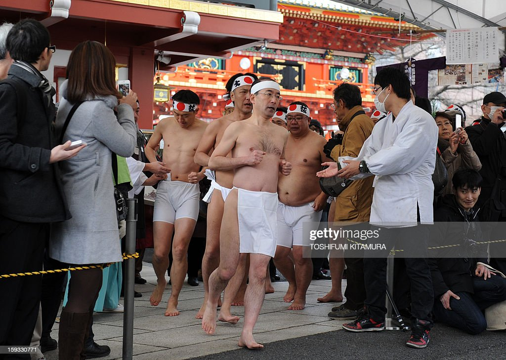 Led by a Shinto priest (C), near-naked believers jog into the site before pouring water over themselves to purify their bodies and souls as part of a new year endurance show at Kanda Shrine, known as Kanda Myojin, in Tokyo on January 12, 2013. About 50 people participated in the annual winter event. AFP PHOTO / TOSHIFUMI KITAMURA