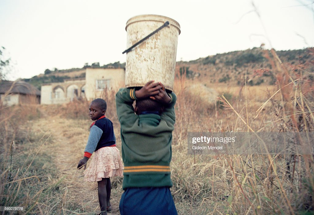Led by elder brother Venda Mamba who has the great responsibility of looking after and feeding his siblings the Mamba AIDS orphans walk in the fading...