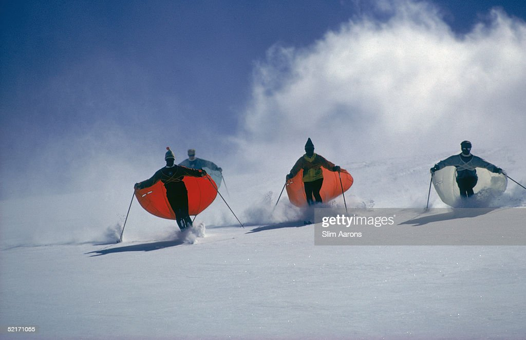 Led by skimaster Stein Eriksen skiers 'sail' down a slope at SnowmassatAspen Colorado circa 1967 The skiers are wearing thin capes which attach to...