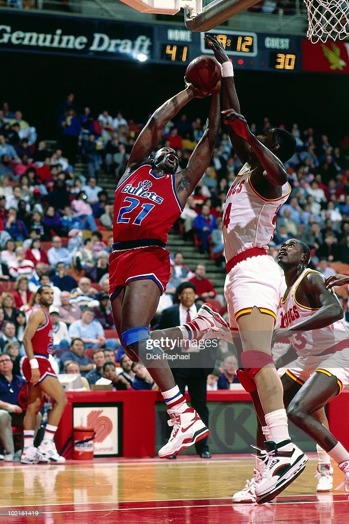 Ledell Eackles #21 of the Washington Bullets goes up for a shot against Hakeem Olajuwon #34 of the Houston Rockets during a game played in 1990 at the Summitt in Houston, Texas.