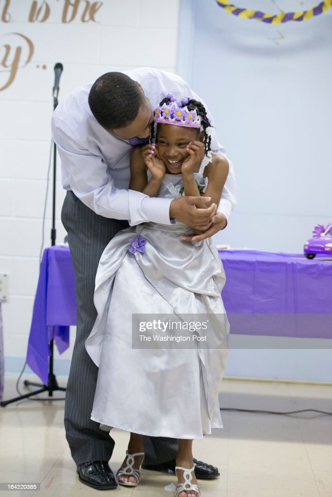 Lee Bassett hugs his daughter Shavondra Harkless, 8, after she freestyle rapped for her father during the second annual Date with Dad event at the Richmond City Jail in Richmond,Virginia on March 16, 2013. Shavondra raps, I'm Fresh. I'm Clean. I'm cutest little girl you ever seen. She was so bashful that the only way she could perform the rap was to cover her face while she did it.We Profile the Date with Dad event sponsored by Camp Divas and held at the Marriott in Richmond, Virginia and particularly the Richmond City Jail. The story is about how these father-daughter dances have come under fire for excluding kids without fathers. But in this case, the dance offers a rare chance for the fathers and daughters to bond.