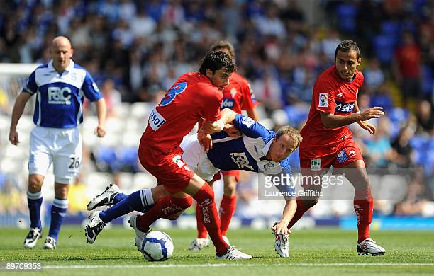 Lee Bowyer of Birmingham City battles with Miguel Michel and Diego Castro of Sporting Gijon during the Pre Season Friendly between Birmingham City...