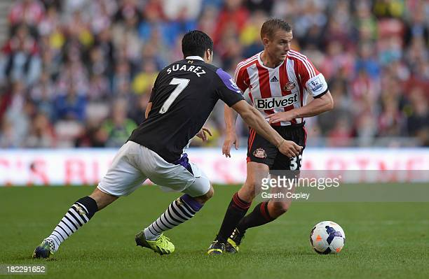Lee Cattermole of Sunderland is closed down by Luis Suarez of Liverpool during the Barclays Premier League match between Sunderland and Liverpool at...