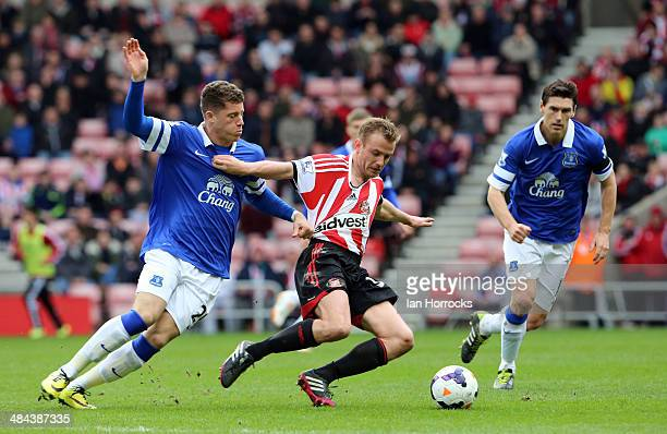 Lee Cattermole of Sunderland is harried by Ross Barkley of Everton with Gareth Barry watching on during the Barclays Premier League match between...