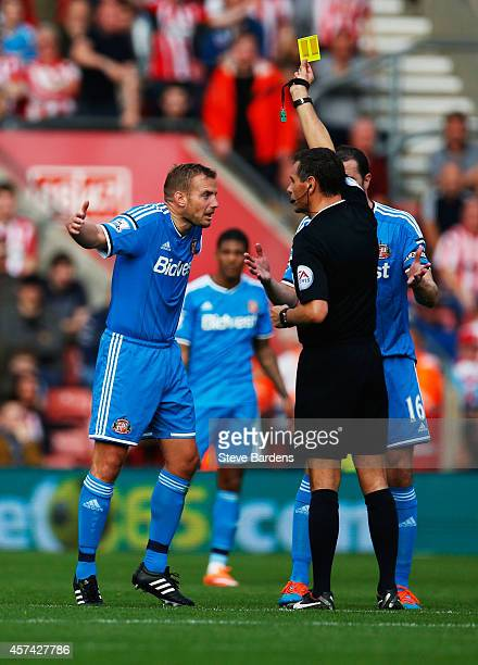 Lee Cattermole of Sunderland is shown a yellow card by referee Andre Marriner during the Barclays Premier League match between Southampton and...