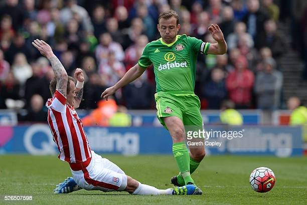 Lee Cattermole of Sunderland is tackled by Glenn Whelan of Stoke City during the Barclays Premier League match between Stoke City and Sunderland at...