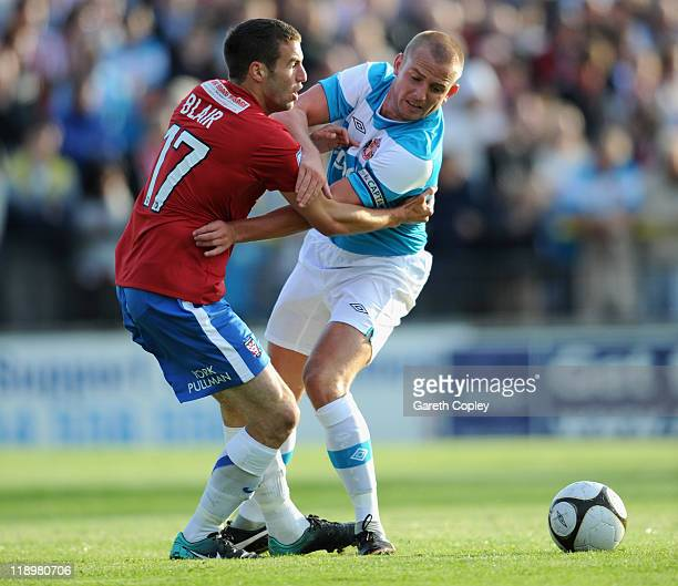 Lee Cattermole of Sunderland is tackled by Matty Blair of York City during the PreSeason friendly match between York City and Sunderland at Bootham...