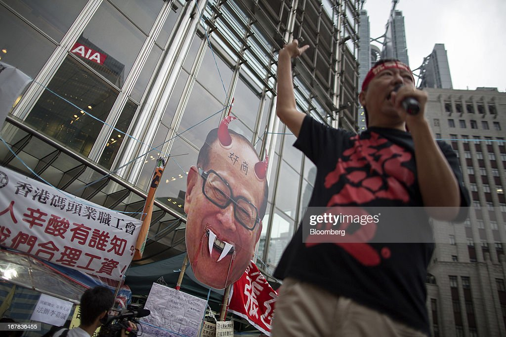 Lee Cheuk-yan, Legislative Council member and general secretary of the Hong Kong Confederation of Trade Unions, chants slogans in front of effigy of billionaire Li Ka-shing, chairman of Hutchison Whampoa Ltd. and Cheung Kong (Holdings) Ltd., outside the Cheung Kong Center during a Labor Day march in Hong Kong, China, on Wednesday, May 1, 2013. Thousands of Hong Kong residents took to the streets today for Labor Day marches to petition for better labor conditions and in support of strike action by workers at docks operated by Li. Photographer: Jerome Favre/Bloomberg via Getty Images