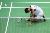 Lee Chong Wei of Malaysia lies on the court injured during the men's singles final match against Lin Dan of China during the Badminton World...