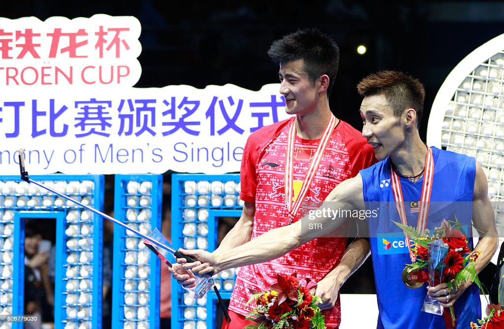 Lee Chong Wei (R) of Malaysia uses a selfie stick to take photos with the runner-up Cheng Long of China on the podium after winning their men's singles final match at the 2016 Badminton Asia Championships in Wuhan, central China's Hubei province on May 1, 2016. / AFP / STR / China OUT