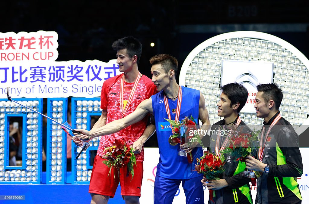 Lee Chong Wei (2nd L) of Malaysia uses a selfie stick to take photos with the runner-up Cheng Long (L) of China and the third place Tian Houwei (3rd L) of China and Lin Dan (R) of China on the podium after winning the men's singles final match against Chen Long of China at the 2016 Badminton Asia Championships in Wuhan, central China's Hubei province on May 1, 2016. / AFP / STR / China OUT