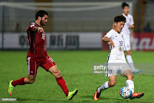Lee Chung Yong of South Korea holds off Mhd Zahir Algunami Almedani of Syria during the 2018 FIFA World Cup Qualifier Final Round Group A match...
