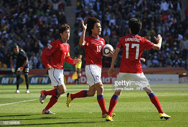 Lee ChungYong of South Korea celebrates scoring his team's first goal with team mates Park ChuYoung and Park JiSung during the 2010 FIFA World Cup...