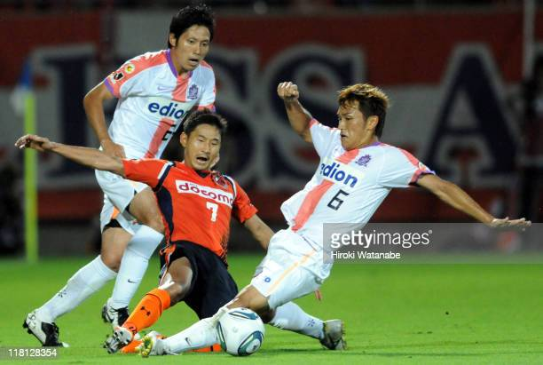 Lee ChunSoo of Omiya Ardija competes for the ball with Toshihiro Aoyama and Ryota Moriwaki of Sanfrecce Hiroshima during the JLeague match between...