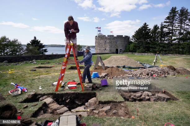 Lee Cranmer takes a photo of a dig site as Kare Mathiasson steadies a ladder for him while the two work an archaeological dig at Colonial Pemaquid...