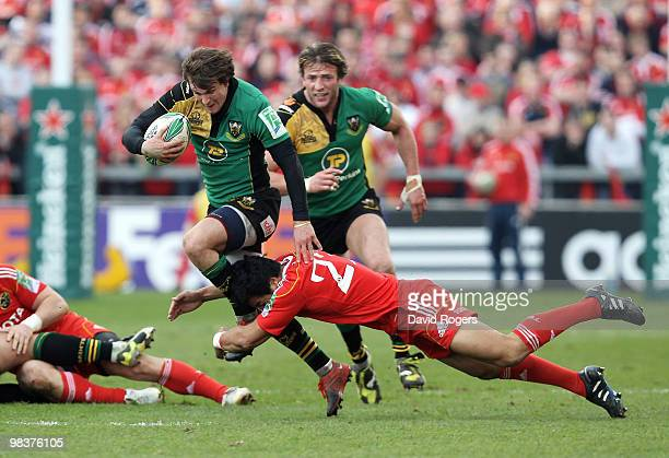 Lee Dickson of Northampton is tackled by Lifeimi Mafi during the Heineken Cup quarter final match between Munster and Northampton Saints at Thomond...