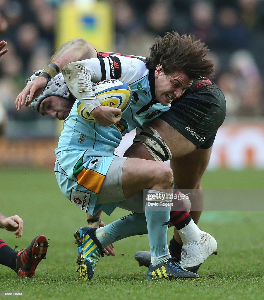 Lee Dickson of Northampton is tackled by Will Fraser during the Aviva Premiership match between Saracens and Northampton Saints at stadiumMK on December 30, 2012 in Milton Keynes, England.