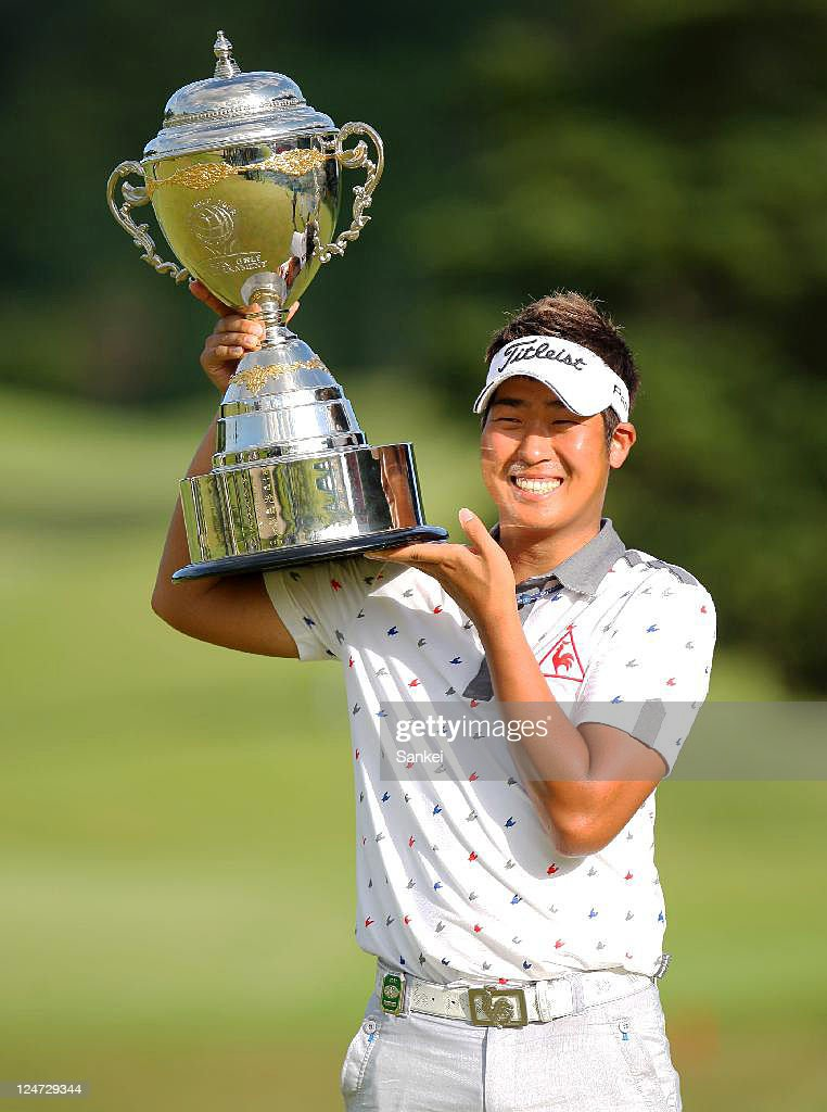 Lee Dong-Hwan poses for photographs after winning the Toshin Golf Tournament at Toshin Lake Wood Country Club on September 11, 2011 in Tsu, Mie, Japan.