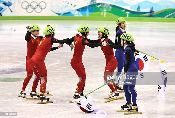 Lee EunByul and Cho HaRi of South Korea looks on as Sun Linlin Zhou Yang Wang Meng and Zhang Hui of China celebrate winning the gold medal after Team...