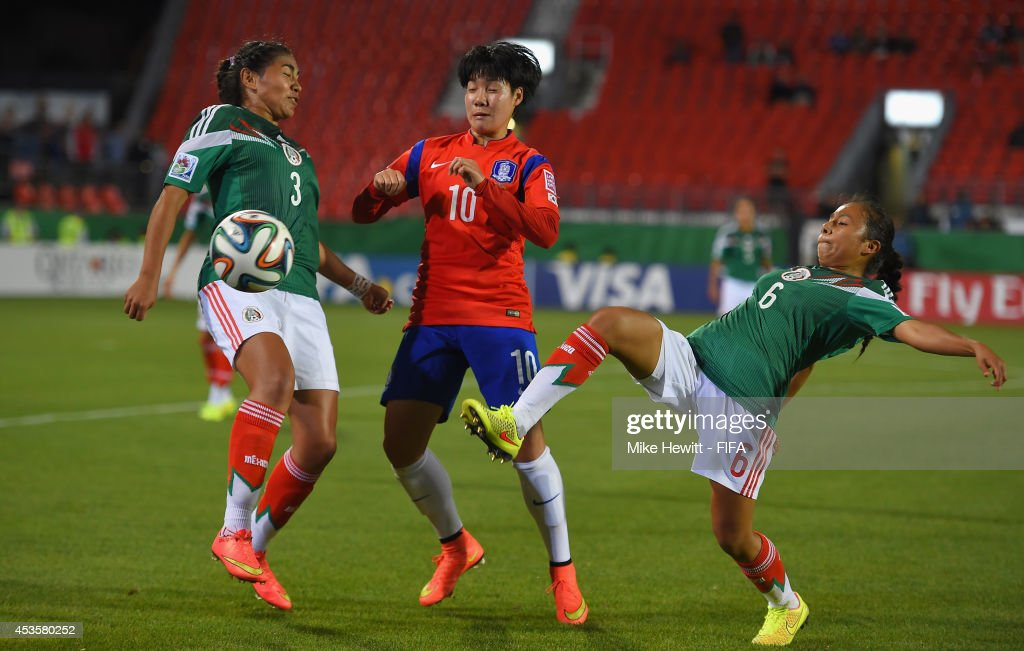 Lee Geummin of Korea battles for the ball with Estefania Fuentes (L) and Karla Nieto of Mexico during the FIFA U-20 Women's World Cup Canada 2014 Group D match between Korea Republic and Mexico at the National Soccer Stadium on August 13, 2014 in Toronto, Canada.