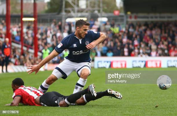 Lee Gregory of Millwall and Josh Clarke of Brentford battle for possession during the Sky Bet Championship match between Brentford and Millwall at...