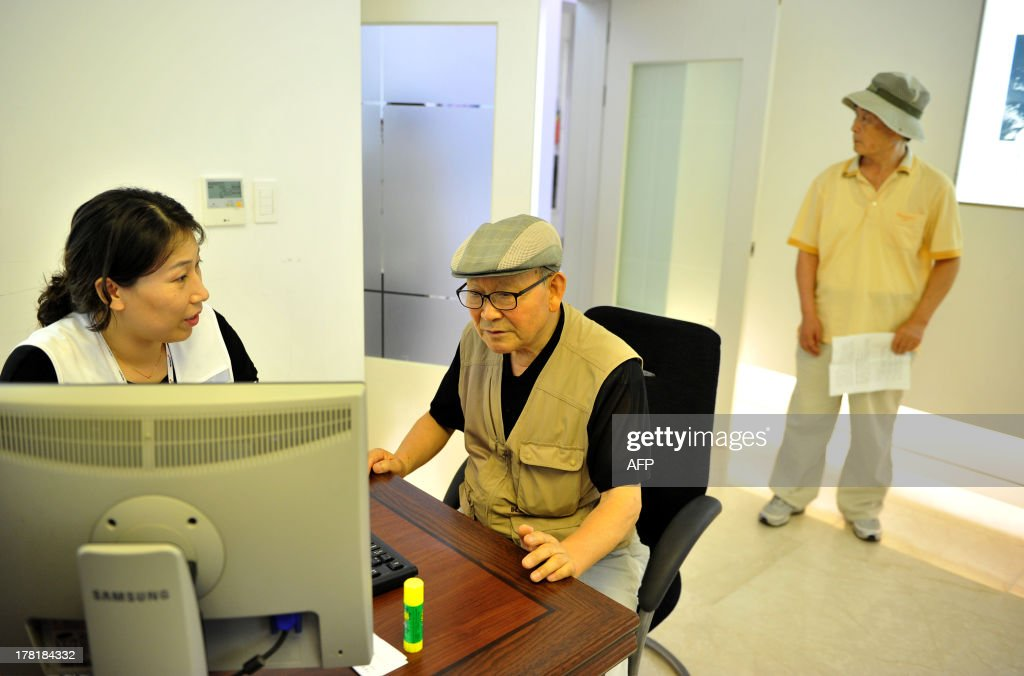 Lee Han Soo (center), 78, checks his application with an official from the Red Cross in Seoul to see if it was possible to take part in upcoming reunions with relatives in North Korea, while Choi Jang Dong (right), 75, waits his turn, at the administration office for separated families at the Red Cross building in Seoul on August 27, 2013; both men were rejected for participation. South Korea's Red Cross on August 24 announced a list of 500 potential candidates for reunions next month with their North Korean relatives separated for decades by the 1950-53 Korean War.