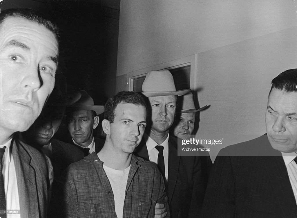 Lee Harvey Oswald (1939 - 1963) (C) is taken into custody by police after allegedly shooting President John F Kennedy, Dallas, Texas.