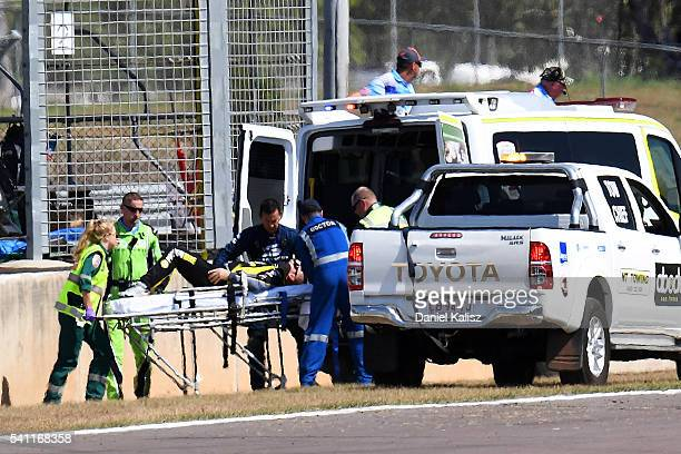 Lee Holdsworth driver of the Preston Hire Racing Holden Commodore VF is stretchered into an ambulance after crashing on the first lap of race 2 for...