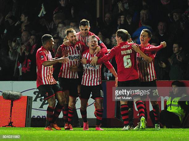 Lee Holmes of Exeter City celebrates with team mates as he scores their second goal during the Emirates FA Cup third round match between Exeter City...