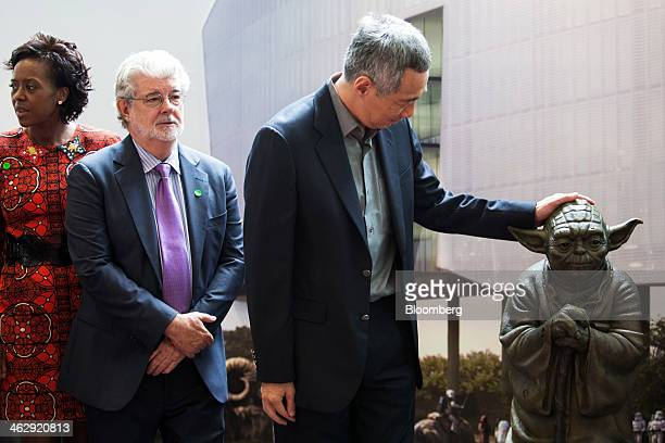 Lee Hsien Loong Singapore's prime minister right pats a statue of Star Wars character Yoda as billionaire George Lucas filmmaker and founder of...