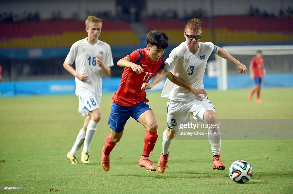 Lee Jiyong of Korea Republic challenges Atli Hrafin Andrason of Iceland during the 2014 FIFA Boys Summer Youth Olympic Football Tournament Semi Final match between Korea Republic and Iceland at Jiangning Sports Centre Stadium on August 24, 2014 in Nanjing, China.