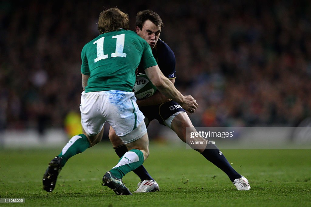 Lee Jones of Scotland is knocked out in a tackle against <a gi-track='captionPersonalityLinkClicked' href=/galleries/search?phrase=Andrew+Trimble&family=editorial&specificpeople=544137 ng-click='$event.stopPropagation()'>Andrew Trimble</a> of Ireland during the RBS Six Nations match between Ireland and Scotland at Aviva Stadium on March 10, 2012 in Dublin, Ireland.