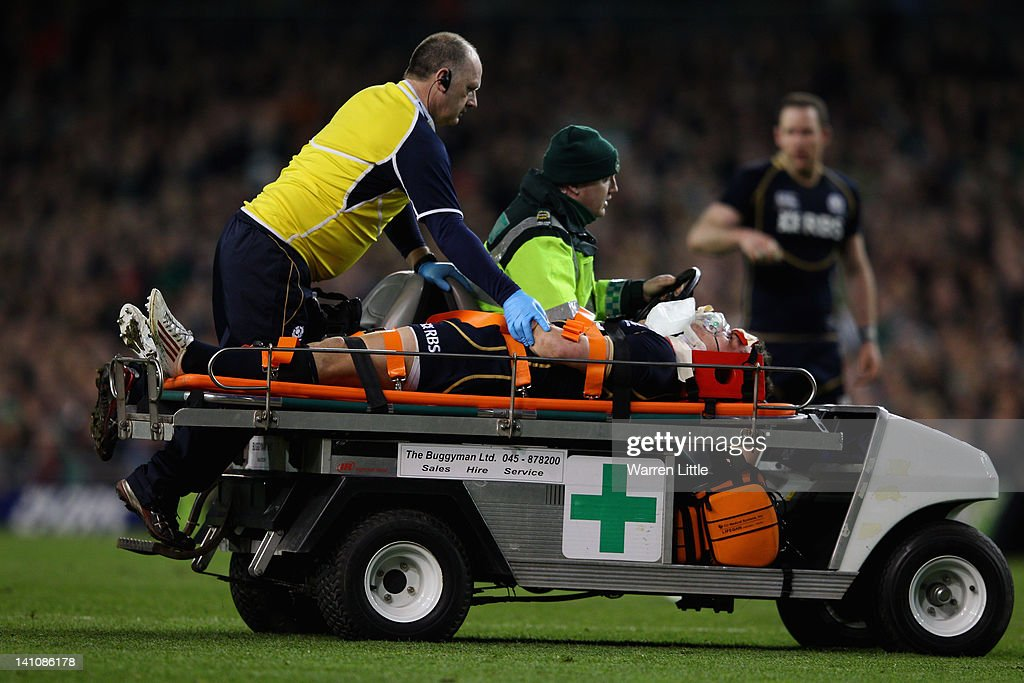Lee Jones of Scotland leaves the pitch after he is knocked out in a tackle against <a gi-track='captionPersonalityLinkClicked' href=/galleries/search?phrase=Andrew+Trimble&family=editorial&specificpeople=544137 ng-click='$event.stopPropagation()'>Andrew Trimble</a> of Ireland during the RBS Six Nations match between Ireland and Scotland at Aviva Stadium on March 10, 2012 in Dublin, Ireland.
