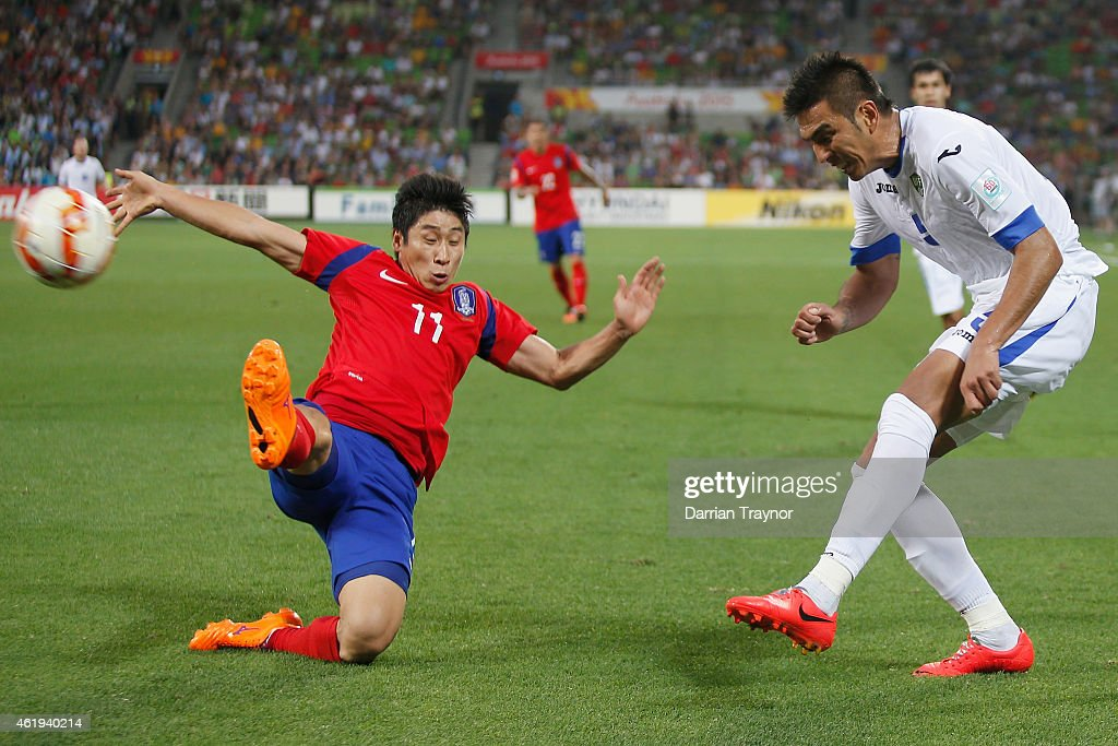 Lee Keun Ho of Korea Republic jumpos to defend a cross from Anzur Ismailov of Uzbekistan during the 2015 Asian Cup match between Korea Republic and Uzbekistan at AAMI Park on January 22, 2015 in Melbourne, Australia.