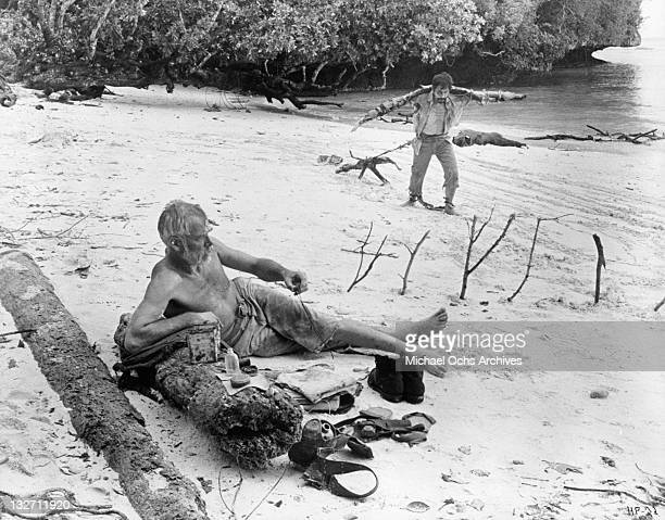 Lee Marvin rests on the beach as Toshiro Mifune struggles on his forced obstacle course march in a scene for the film 'Hell In The Pacific' 1968