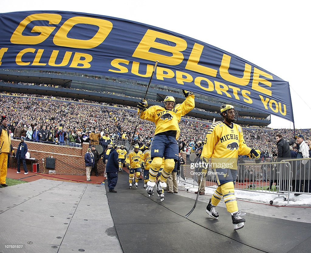 Lee Moffie #13 of the Michigan Wolverines jumps to the Michigan banner on his way to the ice prior to playing Michigan State at Michigan Stadium on December 11, 2010 in Ann Arbor, Michigan.